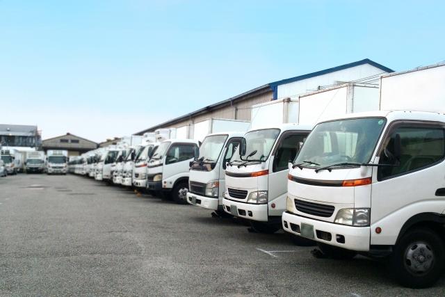 白の配送トラックが10台以上並んでいる