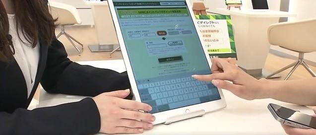 三井住友銀行の行員がお客様にタブレットでオンラインバンキングの使い方を説明